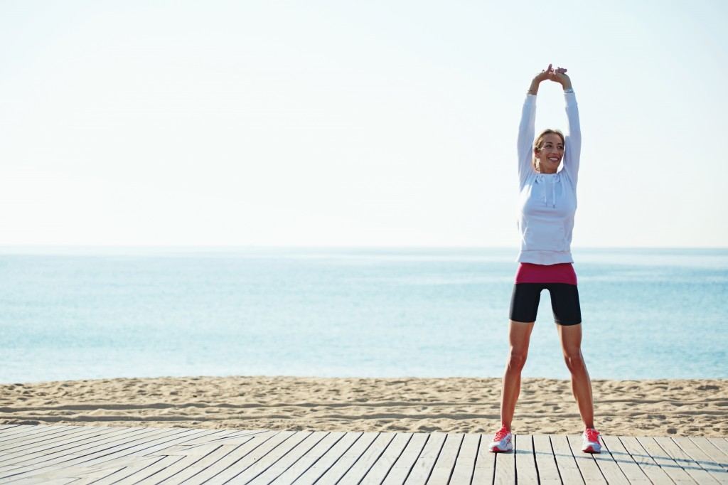 Slim woman in white sportswear doing stretching exercise