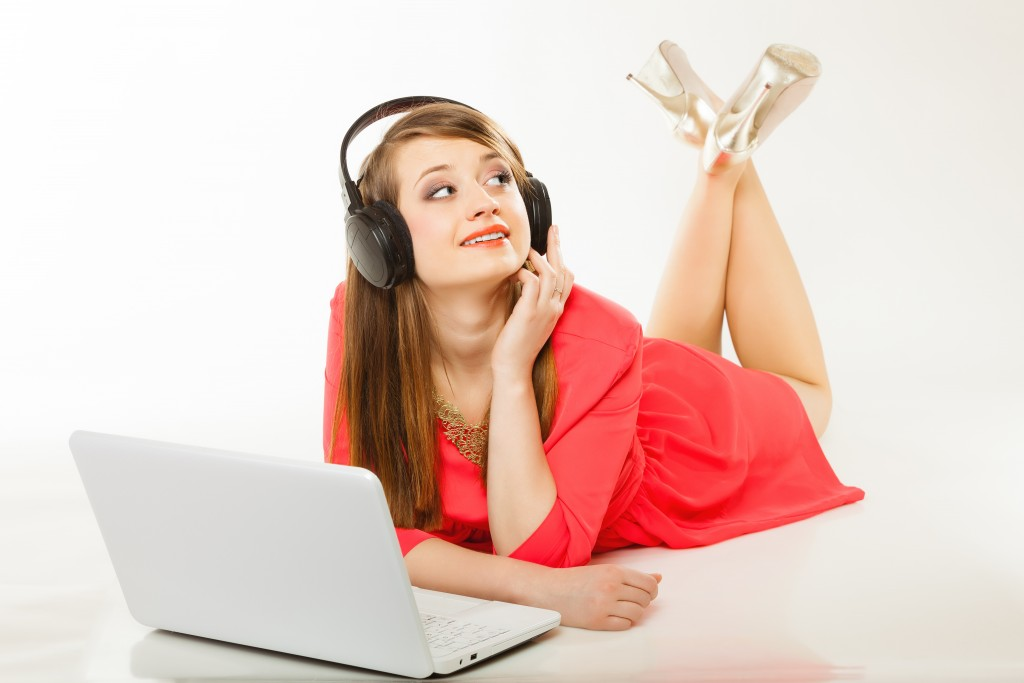 Leisure free time, music, online and internet concept - happy teenage girl with headphones and laptop computer